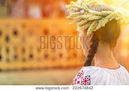 Young woman dressed in a romanian folk port, working manually at a brooch