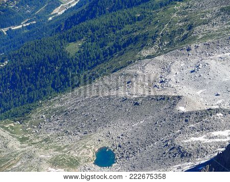 Small lake in valley seen from AIGUILLE du MIDI summit at highest alpine mountains range in french rocky ALPS landscape in FRANCE in 2016 warm sunny summer day, aerial view, Europe on July.