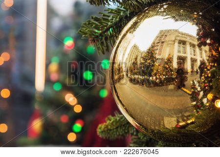 Christmas shiny ball on the Christmas tree at the fair, crowd of people reflected in mirror. Concept christmas and new year holidays