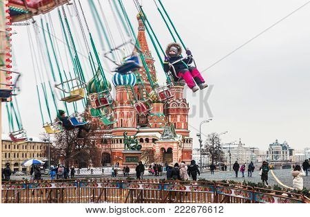 MOSCOW, RUSSIA-January 13, 2018: people swinging on the carousel on the background of the Pokrovsky Cathedral and monument to Minin and Pozharsky. Focus on the monument