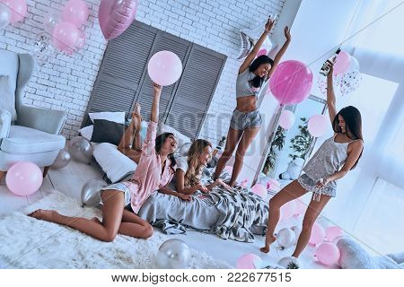 Top view four playful young smiling women in pajamas bonding together while having a slumber party in the bedroom with balloons all over the place