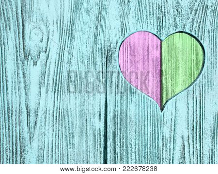 Green and pink heart carved in a wooden board. Background. Postcard, valentine