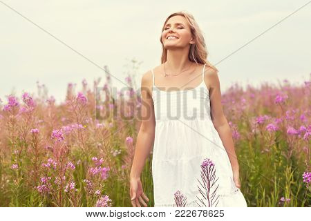 outdoor portrait of a beautiful middle aged blonde woman. attractive sexy girl in a field with flowers