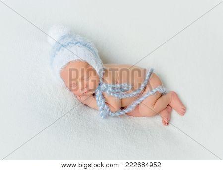 Sweet newborn baby sleeping on white blanket
