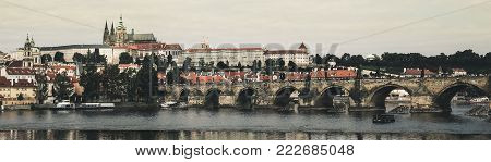 Panorama of Prague with the river Vltava, Charles Bridge, St. Vitus Cathedral and old vintage houses. Photo in retro style