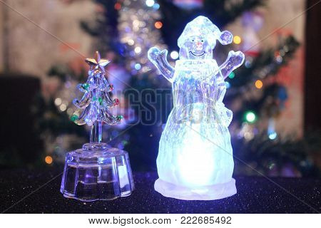 beautiful shine crystal statue of snowman with little glass fir tree shine and sparkling decoration on Christmas and New Year Holiday