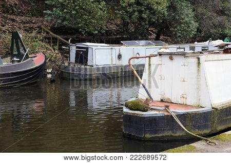 detail of narrowboats and barges moored on a canal