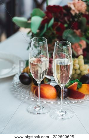 Glasses with champagne drink on a table. Happy newlyweds drinking at ceremony. Loving couple created new family. Decorated alcohol drinks