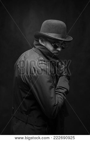 Robber in a hat, glasses and black gloves, black and white frame