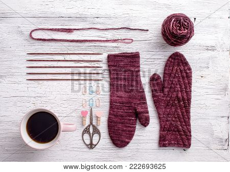 Mittens knitted in dark red yarn with yarn for knitting and knitting needles on a wooden background. Top view. Flat lay. Handmade for winter woolen cloth. Knolling knitting