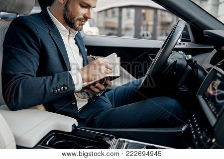 Planning the day. Handsome young man in full suit writing something down in personal organizer while sitting inside of the car