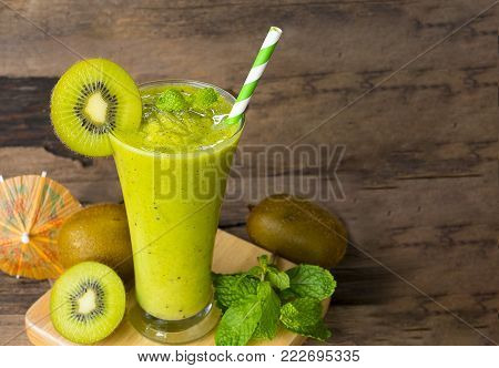 Kiwi smoothies yogurt, juice fruit and Kiwi fruit for breakfast in the morning on a wooden floor.