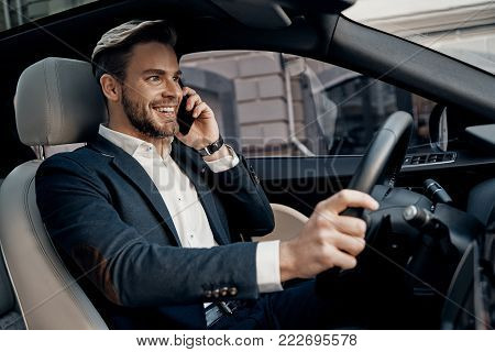 Always available. Handsome young man in formalwear talking on his smart phone and smiling while driving a luxury car