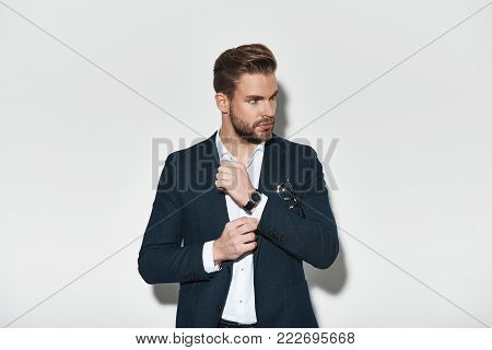 Confident in his style. Handsome young man in full suit adjusting his sleeve and looking away while standing against grey background