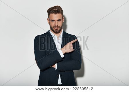 Take a look over there! Handsome young man in full suit pointing copy space and looking at camera with smile while standing against grey background