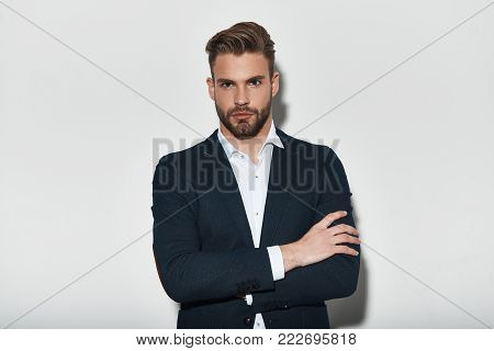 Confident in his perfect style. Handsome young man in full suit keeping arms crossed and looking at camera while standing against grey background