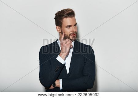 Thinking about... Handsome young man in formalwear looking away with smile while standing against grey background