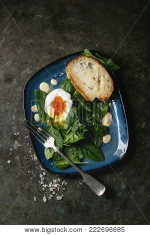 Poached egg on fresh spinach leaves with hollandaise sauce, red caviar and roasted bread served in blue square plate over old dark metal background. Top view, space. Vegetarian healthy eating