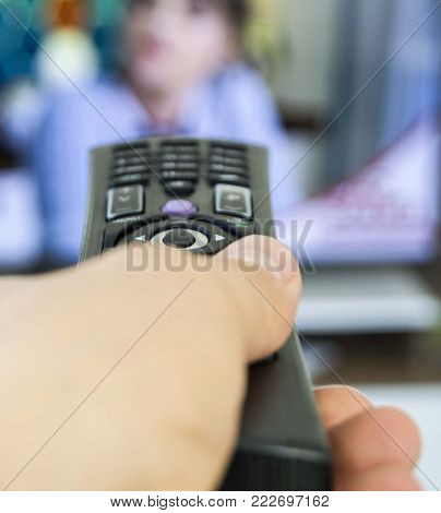 resting at home and watching television, zapping with remote control, watching people watching TV at home