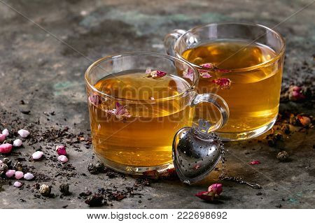 Two glasses of hot tea, rose buds, heart shaped tea strainer, pink sugar over old dark metal background. Space for text. Love Valentines day concept