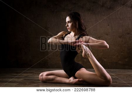 Beautiful Young Girl Dancer With Long Flowing Hair In Black Clothes, A Gymnastic Swimsuit, In A Danc
