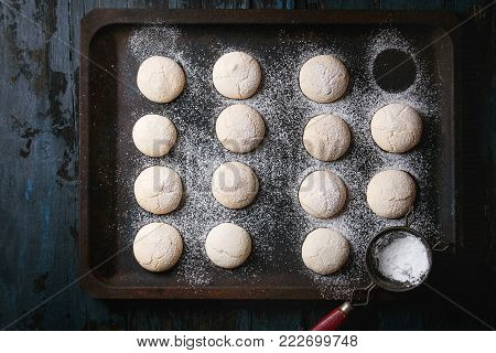 Homemade almond cookies with sugar powder, with vintage sieve, on old oven tray over dark blue wooden table. Dark rustic style. Top view, space