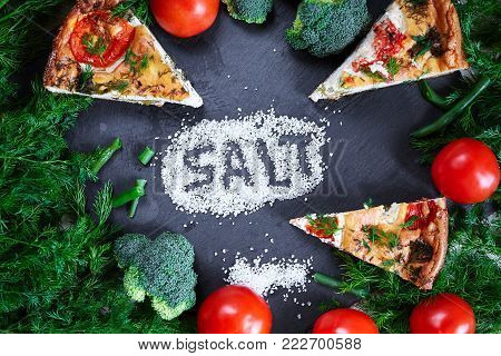 Salt, Vegetables and pieces of vegetable pie with cottage cheese, tomatoes, broccoli, dill and asparagus beans on a dark ceramic background, stone. Vegeterian food concept. The word salt is written in a layer of salt
