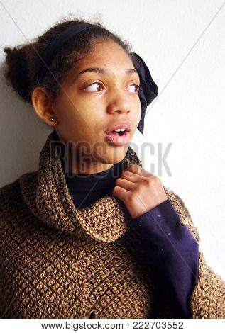 amazed african american girl wrapped in warm poncho made by craftsman with knitting