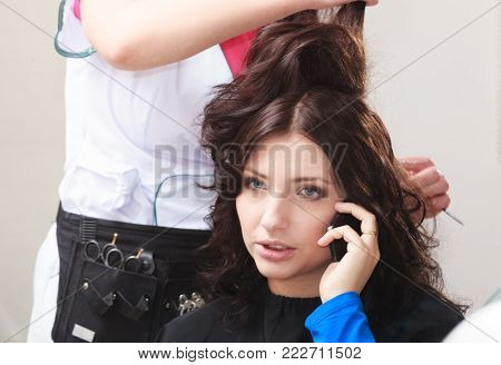 Busy businesswoman by hairstylist. Business woman talking phone in hairdressing beauty salon. Hairdresser combing female client.