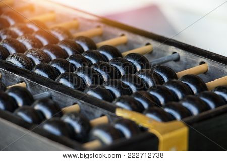 Close up of old vintage retro chinese abacus on wooden table with copy space for background. Vintage chinese abacus counting for finance, business, accounting.