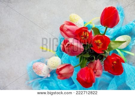 Spring Concept. Colorful Background Of Easter With Tulips, Colored Eggs On A Concrete Background.