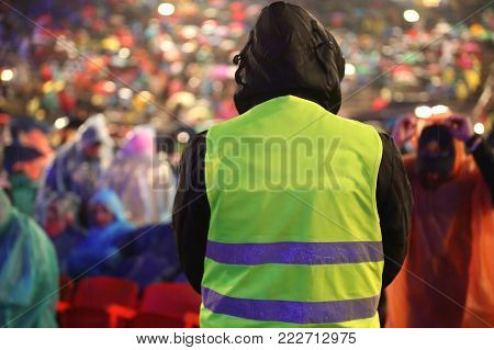 Security Guard With Safety Vest Controls People During An Important Event