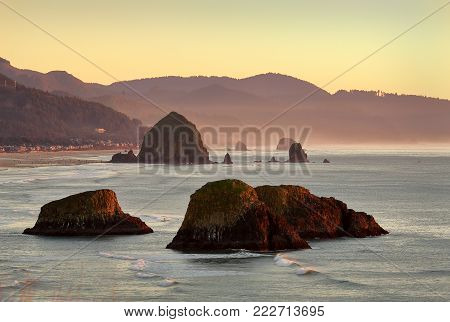 Oregon Coast, Cannon Beach, Dusk USA. High angle view of Cannon Beach at dusk with famous Haystack Rock in the background. Oregon, United States.