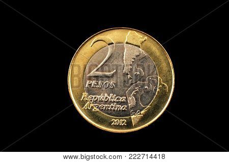 A bimetallic two peso coin from Argentina isolated on a black background