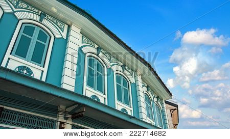 Close up of old vintage windows and roof asian building in Sino Portuguese architecture style with beautiful blue sky and white cloud in background. Blue Sino-Portuguese ancient building with copy space.