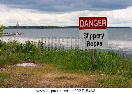 Danger Slippery Rocks sign in grass on the lakeshore in Sibbald Point Park