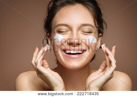 Laughing girl applying moisturizing cream on her face. Photo of young girl with flawless skin on beige background. Skin care and beauty concept