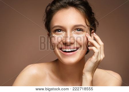 Happy woman touching her skin. Photo of attractive woman with perfect skin on beige background. Beauty & Skin care concept