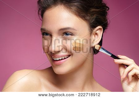 Beautiful woman with tone cream lines on her face. Photo of smiling brunette woman with healthy skin and perfect makeup on pink background. Skin care concept