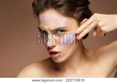 Resolute woman doing makeup using concealer. Photo of beautiful brunette woman on brown background. Skin care concept
