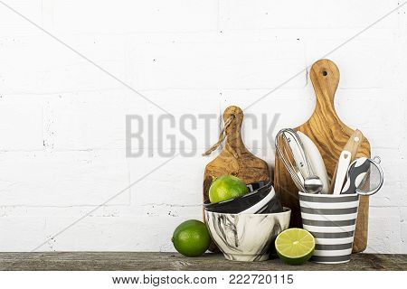 Kitchen tools, olive cutting board on a kitchen shelf against a white brick wall. selective focus.