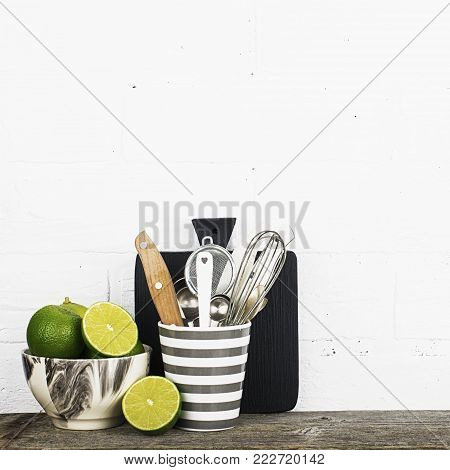 A simple kitchen still life against a white brick wall dishes of modern trendy colors gray, black, white with fresh bright limes. Horizontal. Selective focus
