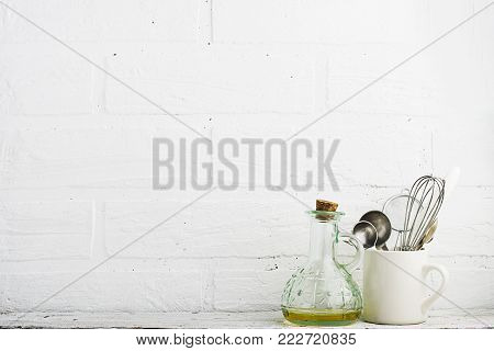 Kitchen tools, olive cutting board on a kitchen shelf against a white brick wall. selective focus,