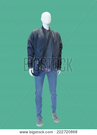Full-length male mannequin dressed in black jacket and blue jeans over green background. No brand names or copyright objects.