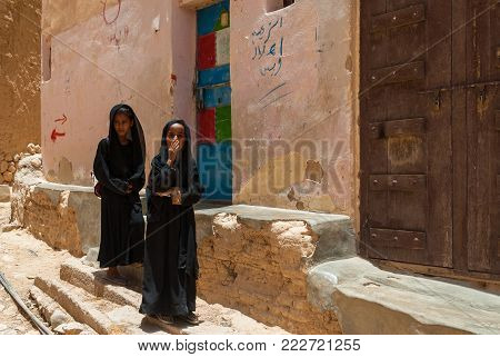 AL HAJARAYN, YEMEN - MAY 4, 2007: Two girls dressed in black return from school on May 4, 2007 in Al Hajarayn, Yemen. Although infant mortality is high, children in Yemen are culturally, socially and religiously valued.