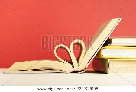 Close up heart shape from paper of book on red background. Valentines day concept.