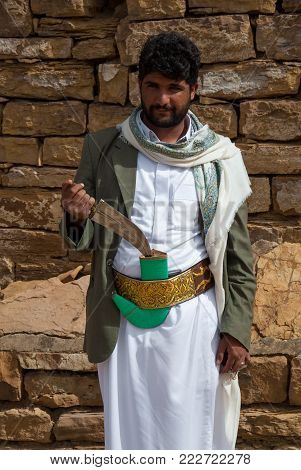 THULA, YEMEN - MAY 5, 2007: A man poses at the camera with his janbiya on May 5, 2006 in Thula, Yemen. Janbiya is a traditional knife that yemeni men typically above the age of 14 wear it as an accessory to their clothing.