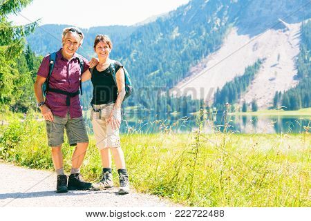 active senior couple is having fun on a hiking trip.