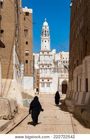 SHIBAM, YEMEN - MAY 8, 2007: Two women dressed in black walk in a street of Shibam, a UNESCO World Heritage Site in Yemen on May 8, 2007. Among other arabic countries, in 2012 Yemen became a site of civil conflicts, which still continue.