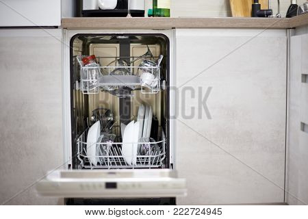 Dishwasher machine in modern kitchen load with plates and glasses